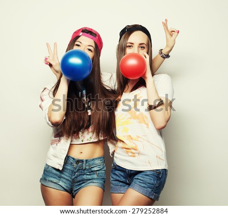 Two happy hipster girls smiling and holding colored balloons over white background - stock photo