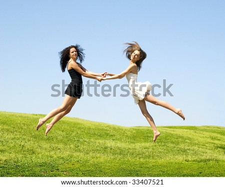 two happy jumping woman against nature background