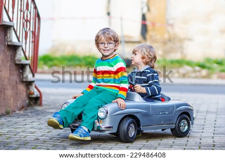 Two happy kid boys playing with big old toy car in summer garden, outdoors. Siblings and friends on warm day. - stock photo