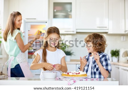 Two happy kids baking a fruit cake with red currants in the kitchen - stock photo