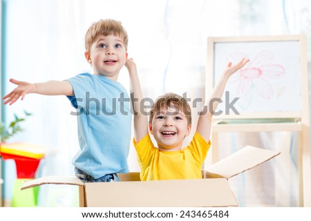 two happy kids boys playing and sitting in cardboard box - stock photo