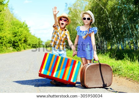 Two happy kids catche a passing car near the road. Adventure and travel. - stock photo