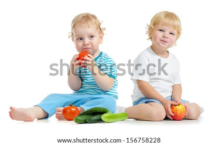 Two happy kids eating healthy food fruits and vegetables - stock photo