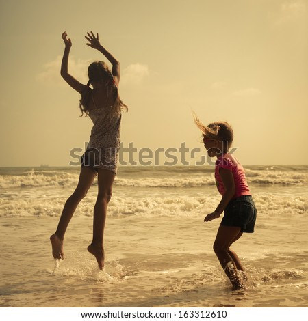 Two happy kids jumping on the beach in the day time - stock photo