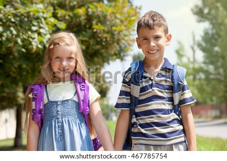 two happy kids on street go together to school
