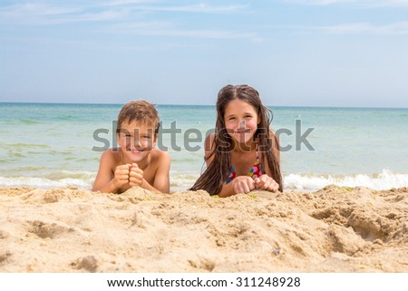 Two happy kids on the beach lying down on the sand near water - stock photo