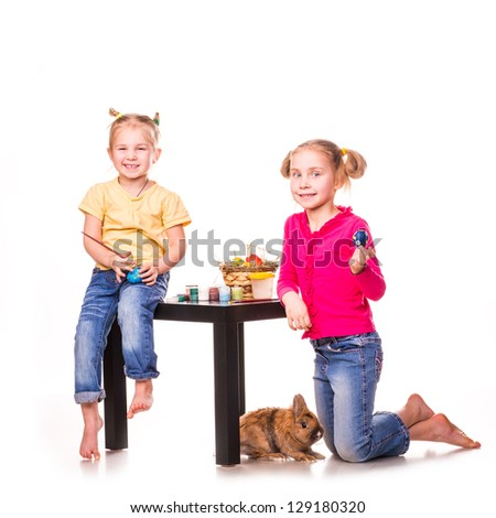 Two happy kids painting easter eggs isolated on white. Happy Easter
