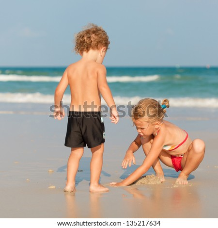 two happy kids playing on beach - stock photo