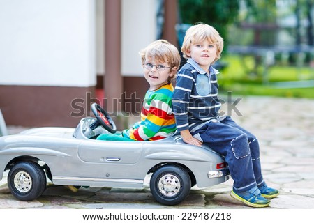 Two happy kids playing with big old toy car in summer garden, outdoors. Siblings and friends on warm day. - stock photo