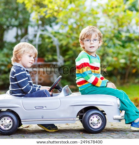 Two happy kids playing with big old toy car in summer garden, outdoors. Twins boys and friends on warm day. - stock photo