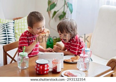 Two happy kids, two brothers, having healthy breakfast sitting at wooden table in sunny kitchen, eating waffles  and watching cartoon on tablet