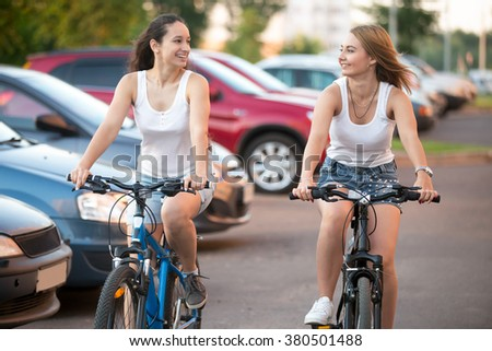 Two happy laughing beautiful blond and brunette young women friends looking at each other, riding in playful bike contest beside parked cars in the city residential area - stock photo