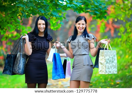 two happy laughing women after shopping