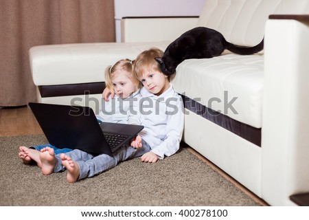 two happy little baby boy and a fair-skinned blonde girl (brother and sister) sitting on the floor with a laptop and watching cartoons on the computer, a cat on a sofa ironed (fins) on kid - stock photo