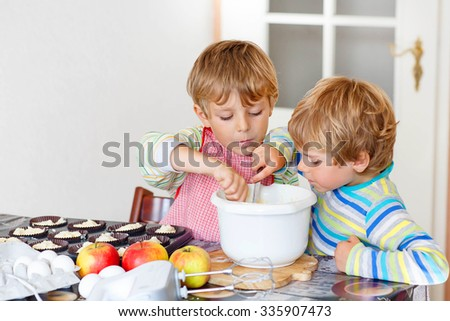 Two happy little blond kid boys baking apple cake in domestic kitchen. Children having fun with working with mixer, eggs and fruits. Tasting dough