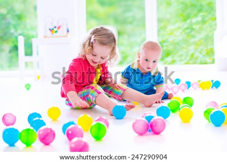 Two happy little children, cute curly toddler girl and a funny baby boy playing together with colorful balls in a white sunny room with big window - stock photo