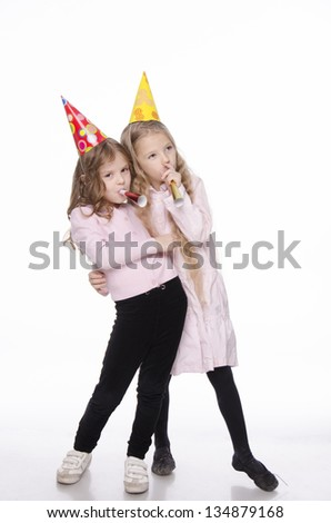 two happy little cute girls with a party whistles