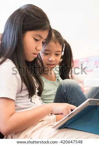 Two happy little girl kid lifestyle playing game on tablet pad mobile digital telecommunication device: Children enjoy using smart IT PC gadget app touch screen wifi wireless technology on playtime - stock photo