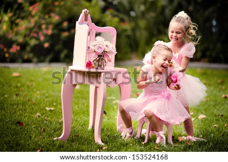 two happy little girl wearing in princess costumes have a fun in a beautiful garden - stock photo