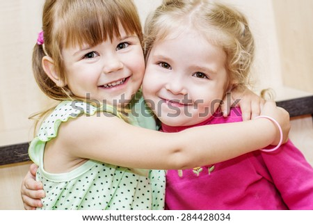 Two happy little girls hugging in the room