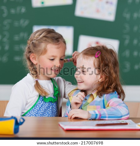 Two happy little girls in school sitting at a desk in front of the blackboard turning to chat to one another - stock photo