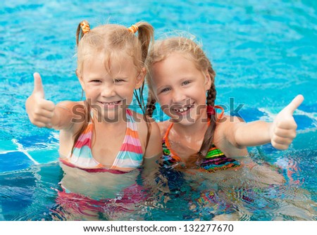 two happy little girls  in the pool - stock photo
