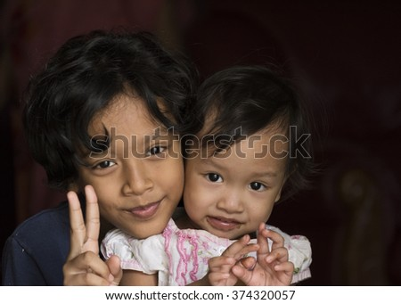 Two happy little girls on black background