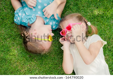 two happy little girls playing in the park in the day time
