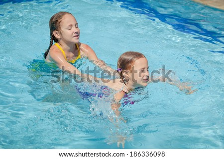 two happy little girls playing  in the pool
