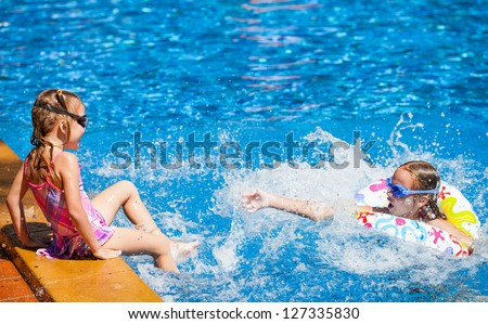 two happy little girls splashing around in the pool - stock photo