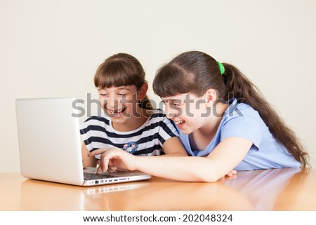 Two happy little girls with laptop