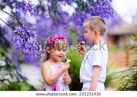 Two happy little kid boy and girl eating ice cream and playing outdoor - stock photo