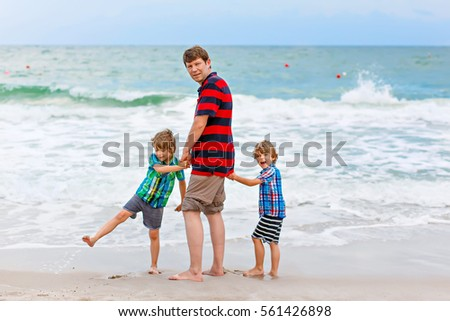 Two Happy Little Kids Boys And Father Standing On The Beach Of Ocean Looking