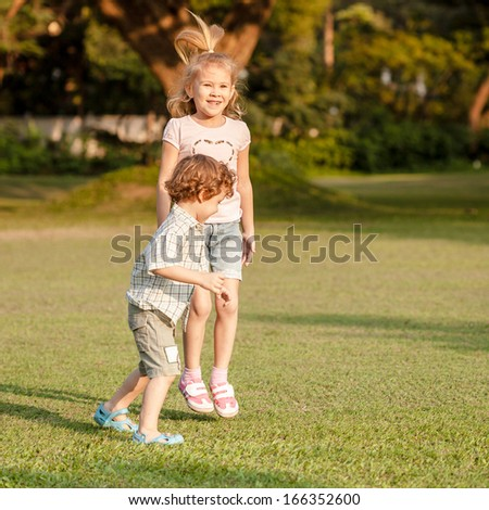 two happy little kids playing in the park in the day time - stock photo