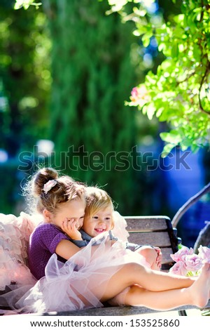 Two happy little sisters hug and play in a beautiful park - stock photo