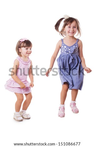 Two happy little sisters jumping in motion isolated on white