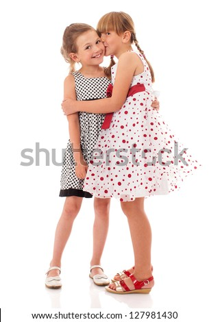 Two happy little sisters kissing isolated on white - stock photo