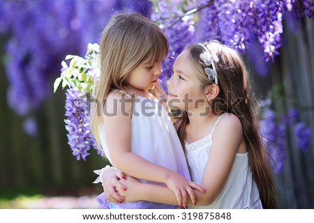 Two happy little sisters love and hug in beautiful park - stock photo