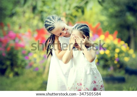 Two happy little sisters playing in the flowers - stock photo