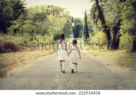 Two happy little sisters walk in the park - stock photo