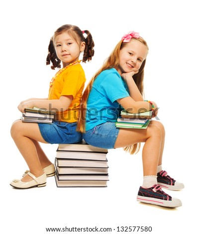 Two happy little 6-7 years old girls Asian and Caucasian sitting on stack books on their hand and smiling standing isolated on white