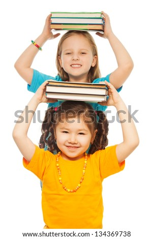 Two happy little 6-7 years old girls holding stack books on their hand and smiling standing isolated on white one behind another - stock photo