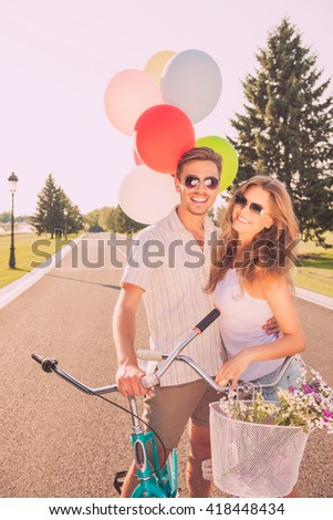 Two happy lovers having holiday and riding bikes - stock photo