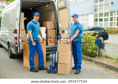 Two Happy Male Worker In Front Of Truck With Stack Of Cardboard Boxes - stock photo
