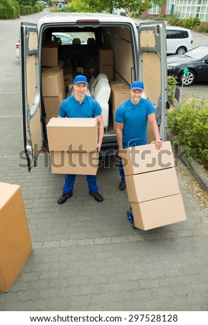 Two Happy Male Workers Loading Stack Of Cardboard Boxes In Truck - stock photo