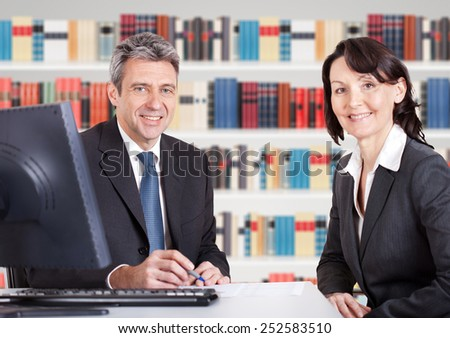 Two Happy Mature Businesspeople Sitting At Office Desk - stock photo