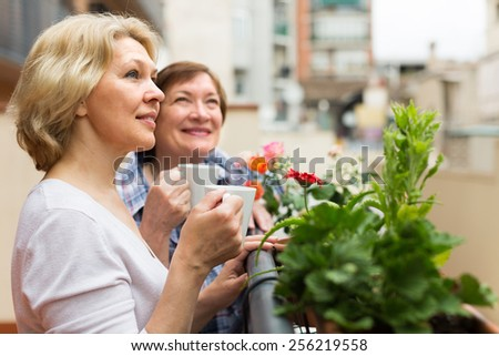 Two happy mature pensioners drinking tea on balcony and smiling - stock photo