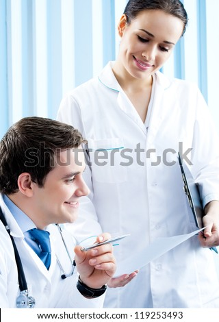 Two happy medical people working together at office