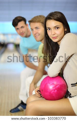 Two happy men and woman sit in bowling club; girl holds pink ball; focus on woman; shallow depth of field - stock photo