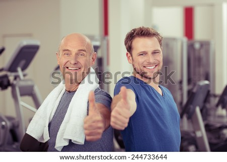 Two happy men, one elderly and one young, in a gym giving a thumbs up of approval and success in a healthy lifestyle and fitness concept - stock photo
